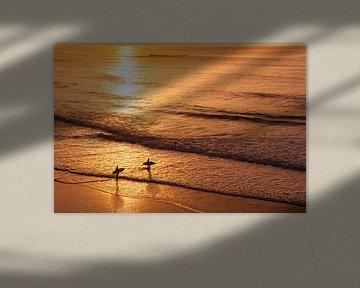 Surfers bij zonsondergang op strand in de Algarve, Portugal