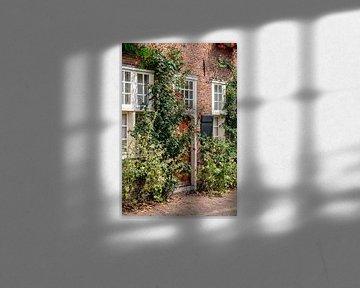 Voorkant bakstenen huis met houten deur en rozenstruik en stokrozen