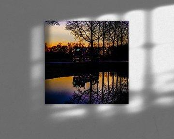 Verlichte vrachtwagen wordt bij zonsondergang weerspiegeld in het water van de Linge van Anne Ponsen