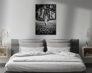 Zwart-wit foto van rennend meisje met vlechtjes op bos pad van Mayra Pama-Luiten