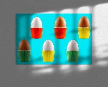 Bunte Vintage-Eierbecher mit Eiern auf blauem Hintergrund von Peter de Kievith Fotografie