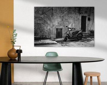 Roller vor einer rustikalen Mauer in einer Stadt in Italien in schwarz und weiß von iPics Photography
