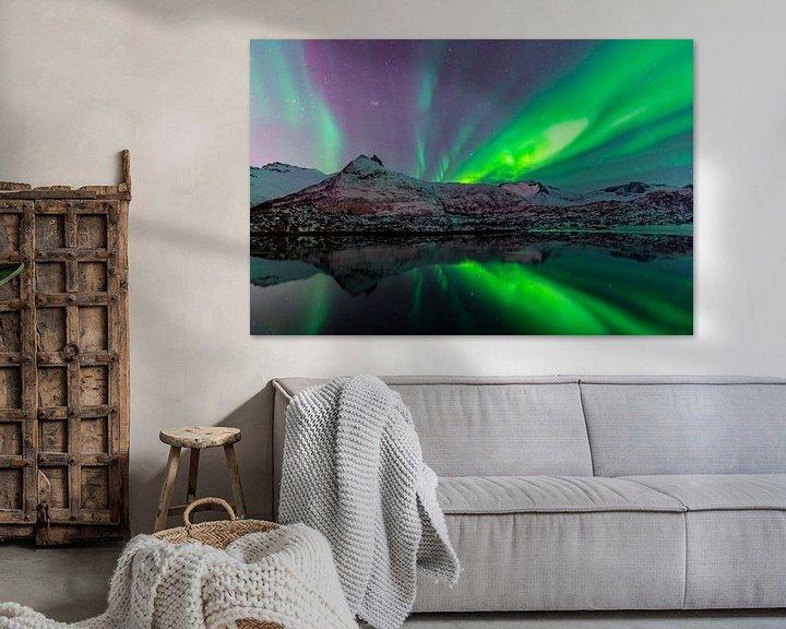 Impression: Aurore boréale ou Aurora Borealis sur un lac aux montagnes enneigées en hiver sur Sjoerd van der Wal