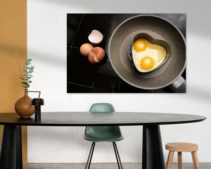 Sfeerimpressie: Twee gebakken eieren in hartvorm op een koekenpan en lege schalen op het zwarte fornuis, koken met l van Maren Winter