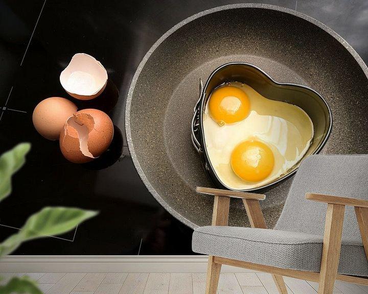 Sfeerimpressie behang: Twee gebakken eieren in hartvorm op een koekenpan en lege schalen op het zwarte fornuis, koken met l van Maren Winter