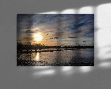 Zakkende zon met reflectie in het water en een bewolkte hemel boven een donker moeraslandschap op ee van Maren Winter