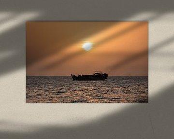 Tanzaniaanse  boot vaart tijdens zonsondergang rustig langs de kust van Stone Town van Michiel Ton