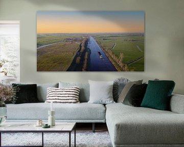Scheepvaart in Groningen bij zonsondergang van Raymond Bos