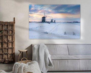 Drie molens bij zonsopkomst in een winter landschap