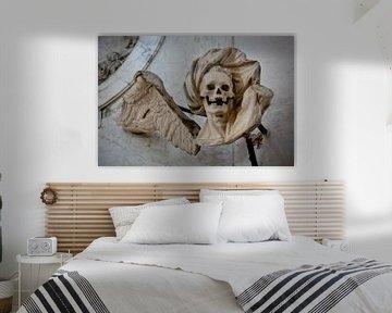 Beeld van engel met doodshoofd schedel, Lübeck, Duitsland van Joost Adriaanse