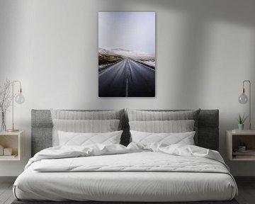 Een weg leidt door een besneeuwd landschap op de Faeröer van Moniek Kuipers