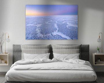 Schöne Strukturen auf einem eisbedeckten IJsselmeer im Winter. Am Horizont geht die Sonne langsam au von Bas Meelker