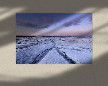 IJs bedekt de Waddenzee in de winter aan de Groningse Waddenkust tijdens zonsondergang. De ondergaan van Bas Meelker