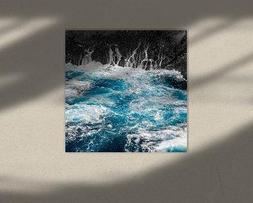 Blauwe oceaangolven en zwarte rotsen