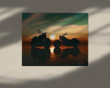 Twee motorfietsen op het strand bij zonsondergang