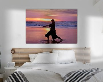 Junge Samurai Frau mit japanischen Schwert (Katana) bei Sonnenuntergang am StrandUntergang am Strand von Nisangha Masselink