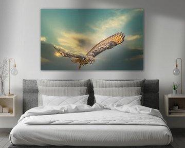Een Euraziatische oehoe of oehoe. Vliegt met uitgespreide vleugels tegen een dramatische hemel. van Gea Veenstra