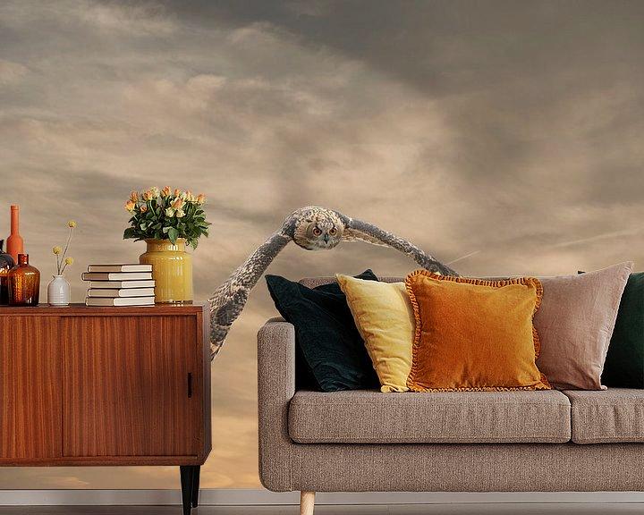 Sfeerimpressie behang: Een Euraziatische oehoe of oehoe. Vliegt met uitgespreide vleugels tegen een dramatische bruin goude van Gea Veenstra