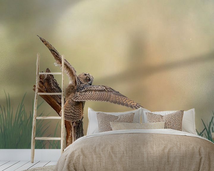 Sfeerimpressie behang: Een gedetailleerde Oehoe met gespreide vleugels land op een boomstronk. Bruin gele lucht met gras in van Gea Veenstra