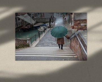 Dame met paraplu langs kanaal in centrum Venetie, Italie met veel regen van Joost Adriaanse