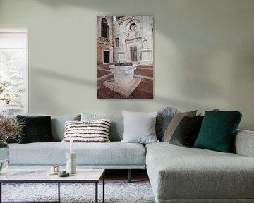 Waterput voor kerk (Abbazia della Misericordia) in centrum van Venetie, Italie van Joost Adriaanse