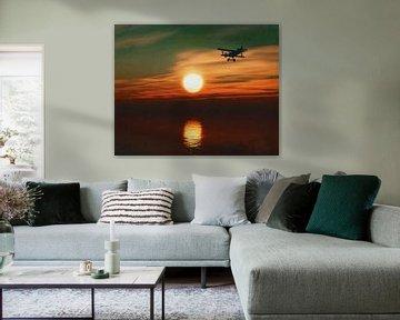 Vliegtuig bij zonsondergang over zee