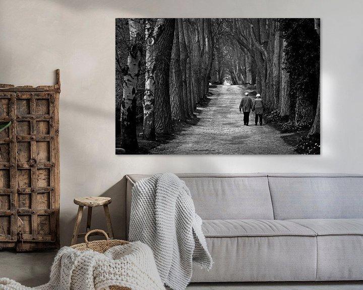 Sfeerimpressie: Oud koppel dat samen langs een lange laan wandelt van Frank Herrmann