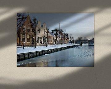 Winterse aanblik van een rij historische huizen en molen in Sloten van Henk Vrieselaar