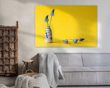 Antike chinesische Vase mit blauen Trauben vor gelbem Hintergrund von Marjolein Hameleers