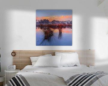 Zonsopgang met blauwe hemel en dramatische wolken weerspiegeld in een meer van Tony Vingerhoets