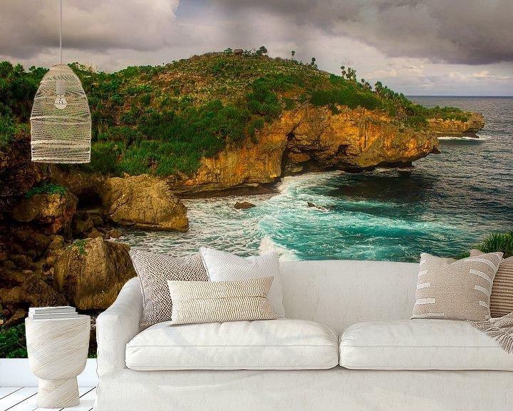 Sfeerimpressie behang: Uitzicht vanaf de heuvelrand op groen rotsstrand en golvende zee. De golven slaan tegen het zandstra van kall3bu