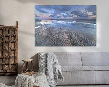 Eb op het strand van Westerschouwen op Schouwen Duivenland in Zeeland. De wolken weerspiegelen in he van Bas Meelker