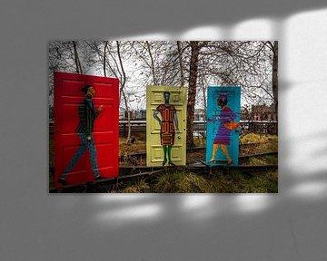 Malerei von afroamerikanischen männlichen und weiblichen Figuren auf roten, gelben und blauen Türen  von Mohamed Abdelrazek
