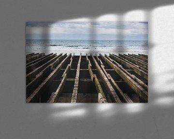 Houten balken kijken uit over de Noordzee van Nederland van Rik Pijnenburg