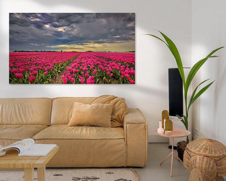 Sfeerimpressie: wolkendek met onweer boven een bloemenveld met tulpen van eric van der eijk