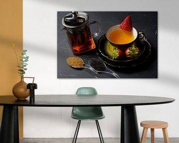 Thé noir avec fraise dans une tasse et un pot en verre avec du thé sur Babetts Bildergalerie