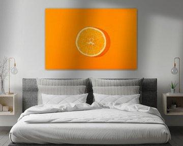 Schijfje sinaasappel tegen een oranje achtergond van Ans van Heck