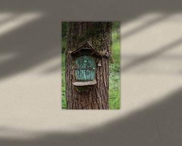 miniatuur huisje met groene deur gemaakt in een boom in een bos