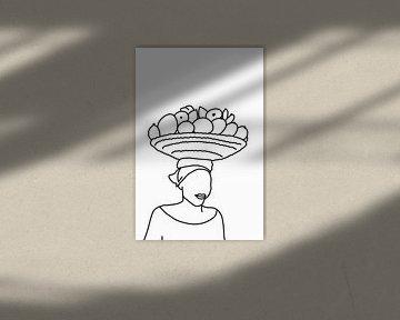 Une femme porte un panier de fruits sur sa tête