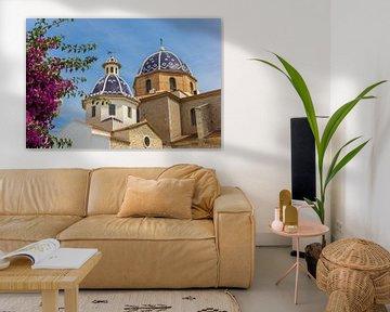 Roze bloemen voor de blauwe koepels van de kerk in Altea van Marc Venema