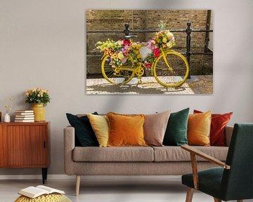 Ein altes gelbes, mit Blumen geschmücktes Fahrrad steht am Zaun einer Gracht in Gouda von Marc Venema