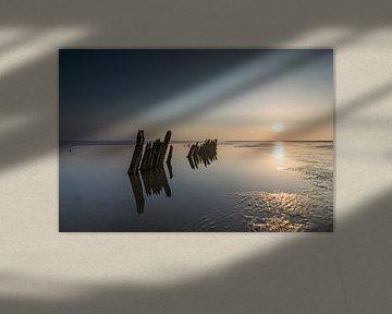 Poteaux dans la mer au crépuscule sur Patrick Verhoef