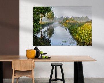 Een kalm riviertje stroomt door het landschap van Jan van der Wolf