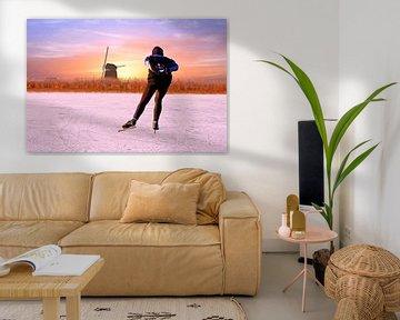 Schaatsen bij de molen bij zonsondergang in Nederland in de winter van Nisangha Masselink