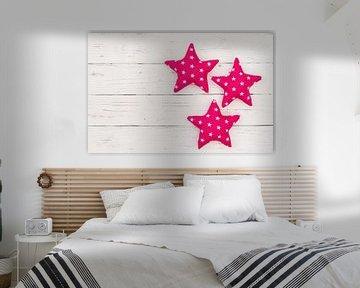 Décoration avec trois étoiles roses sur bois blanc avec espace pour copie sur Alex Winter