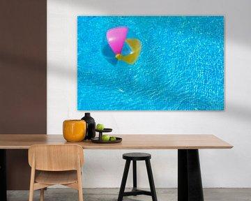 Opblaasbare kleurrijke strandbal vlotter op gegolfd blauw zwembad van Alex Winter