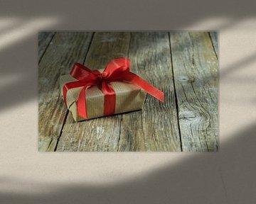 Enkele geschenkdoos met strik van rood lint op hout van Alex Winter