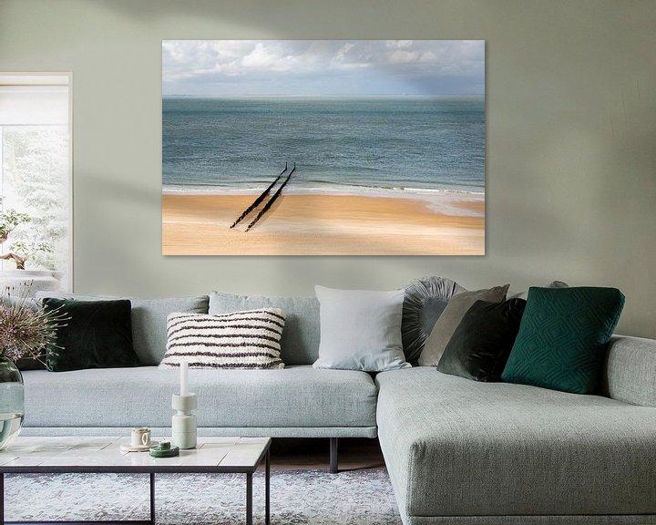 Sfeerimpressie: Een verlaten strand bij Zoutelande met een rij golfbrekers van Kim Willems